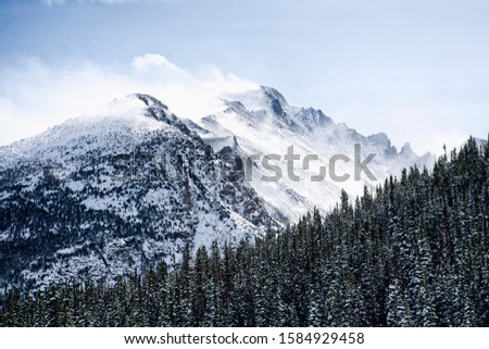 snow covered mountains surrounded by pine trees in the winter. The rocky mountains in Estes Park, CO, USA #1584929458