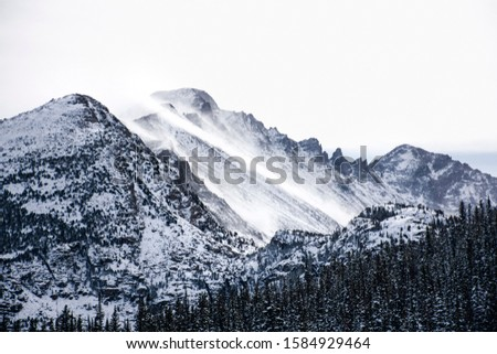 snow covered mountains surrounded by pine trees in the winter. The rocky mountains in Estes Park, CO, USA #1584929464