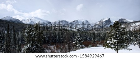 snow covered mountains surrounded by pine trees in the winter. The rocky mountains in Estes Park, CO, USA #1584929467