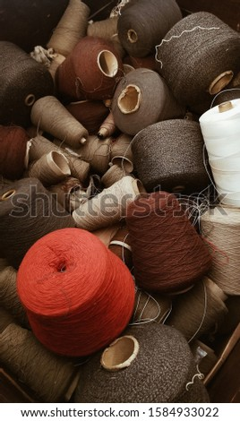 A vertical shot of a lot of thread spools of different colors and sizes #1584933022