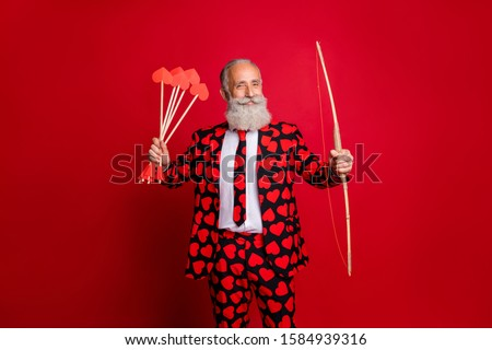 Photo of crazy cupid mature handsome guy valentine day hold bow arrow ready to shoot loving couple wear hearts pattern stylish suit tie trousers blazer isolated red color background #1584939316