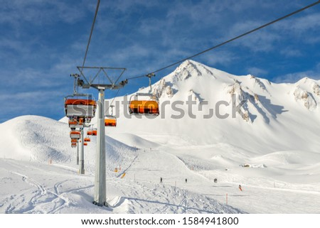 Ski lift ropeway on hilghland alpine mountain winter resort on bright sunny day. Ski chairlift cable way with people enjoy skiing and snowboarding.Banner panoramic wide view of downhill slopes #1584941800