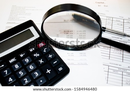 A finance still life with a jar of Sterling coins on Sterling notes, calculator and pen. #1584946480