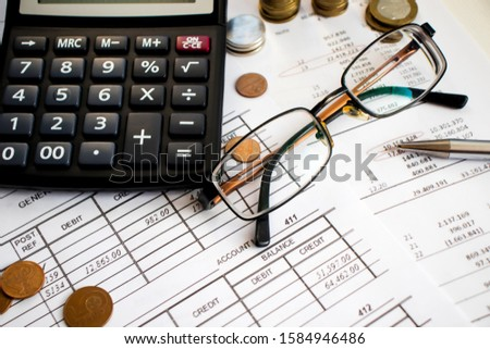 A finance still life with a jar of Sterling coins on Sterling notes, calculator and pen. #1584946486