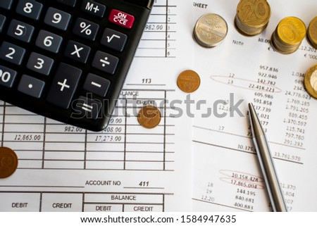 A finance still life with a jar of Sterling coins on Sterling notes, calculator and pen. #1584947635