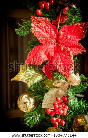 Conceptual picture as background for christmas. Fir branches, golden Christmas balls, poinsettia and some red berries.