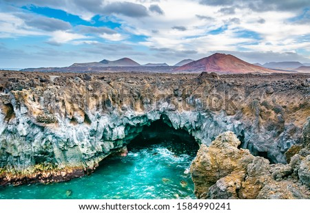Amazing view of lava's caves Los Hervideros and volcanoes in Lanzarote island, popular touristic attraction. Location: Lanzarote, Canary Islands, Spain. Artistic picture. Beauty world. Travel concept.