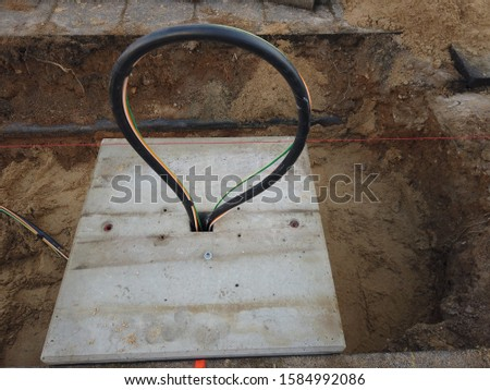 Cable repairement. Open trench with coil of electric and data cables mountedin the hole of the concrete slab #1584992086