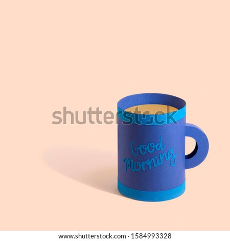 Blue paper mug with tea. Inscription on cup Good morning. Paper art and craft. Volumetric handmade paper objects. Minimal food concept. Square image