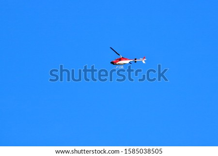 A small two seater commercial helicopter set against a clear, blue sky passes from right to left.  #1585038505