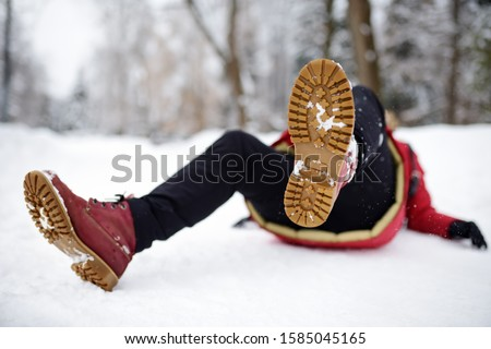 Shot of person during falling in snowy winter park. Woman slip on the icy path, fell and lies. Danger of season trauma. Royalty-Free Stock Photo #1585045165