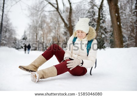 Shot of person during falling in snowy winter park. Woman slip on the icy path, fell, injury knee and sitting in the snow. Danger of season trauma. Royalty-Free Stock Photo #1585046080