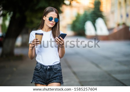 Young woman with coffee to go and phone walking on the summer street #1585257604