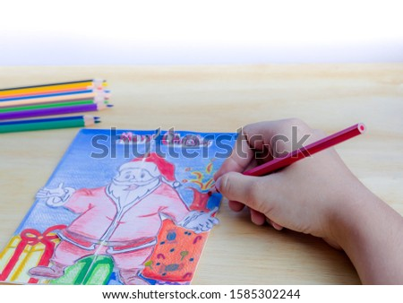Woman's hand drawing of a Christmas greeting card for Christmas celebration with colorful crayons. Handmade Christmas gift ideas