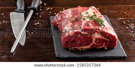 Raw meat. Beef tenderloin, neck lies on a black board, next to a knife and knife sharpener. closeup. background image. copy space