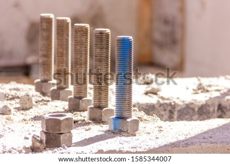 View of the steel anchor bolts and bolt nuts in the concrete foundation in the construction site. are used to connect structural and non-structural elements to the concrete. #1585344007