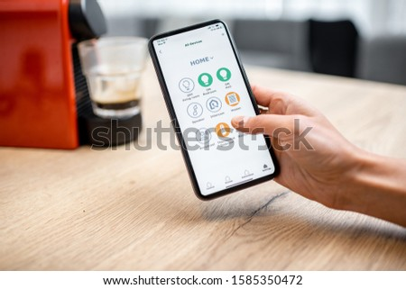 Modern coffee machine connected online with smartphone application. Concept of a smart home and mobile application for managing devices at home #1585350472