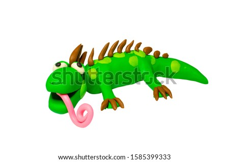 Statues like cute animals for children. Molding from plasticine. Cartoon characters, Iguana isolated on white background wiht clipping path.