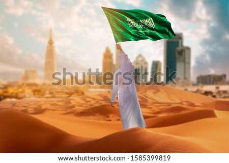 Saudi young Arab man holding Saudi Arabia  flag, celebrating the national day Royalty-Free Stock Photo #1585399819