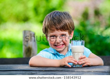 Young little and cute boy pictured with glass of milk.