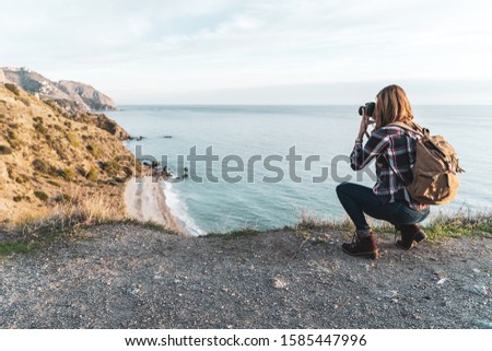 Young hip woman with a backpack exploring and photographing the coast on a beautiful day. Concept of exploration and adventures #1585447996