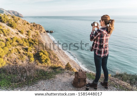 Young hip woman with a backpack exploring and photographing the coast on a beautiful day. Concept of exploration and adventures #1585448017