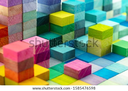 Spectrum of stacked multi-colored wooden blocks. Background or cover for something creative, diverse, expanding,  rising or growing. shallow depth of field. Royalty-Free Stock Photo #1585476598