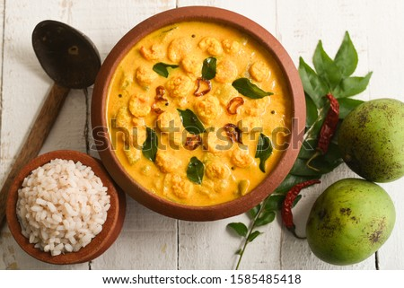 Prawn mango curry recipe and rice Chemmeen Manga shrimp in coconut milk. Spicy Kerala fish curry on white background South India. Top view popular Indian seafood, non veg food side dish for appam