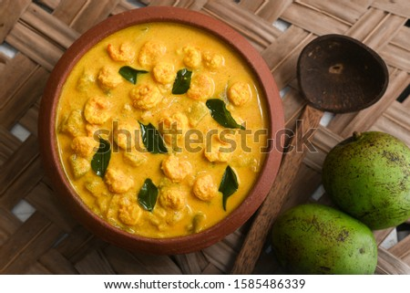 Prawn mango curry recipe, Chemmeen Manga shrimp in coconut milk. Spicy Kerala fish curry on palm mat background South India. Top view popular Indian seafood, non veg food side dish for rice, appam