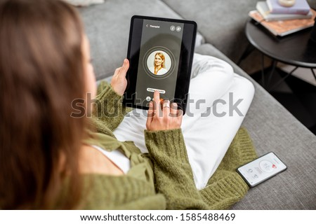 Woman making video call to a doctor using digital tablet, feeling bad at home. Concept of telemedicine and patient counseling online #1585488469