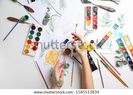 Artist painting picture at table