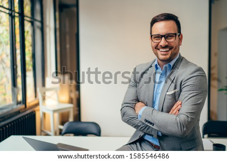Portrait of young happy businessman wearing grey suit and blue shirt standing in his office and smiling with arms crossed Royalty-Free Stock Photo #1585546486