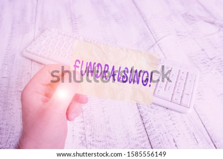 Text sign showing Fundraising. Conceptual photo seeking to generate financial support for charity or cause man holding colorful reminder square shaped paper white keyboard wood floor. #1585556149