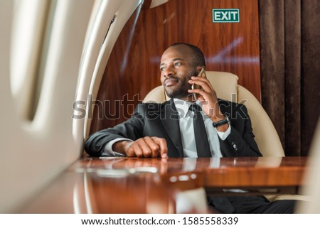 selective focus of handsome african american businessman talking on smartphone in private jet  #1585558339