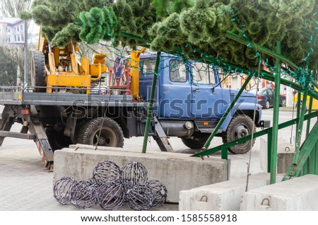 Preparations for decorating a large street Christmas tree. Aerial platform stands next to the Christmas tree. Garlands lie under the Christmas tree. Side view.  Preparing for the New Year holidays. #1585558918