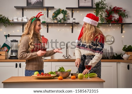 Happy woman with glass and girl cuts celery for New Year in kitchen decorated with Christmas wreaths and garlands #1585672315