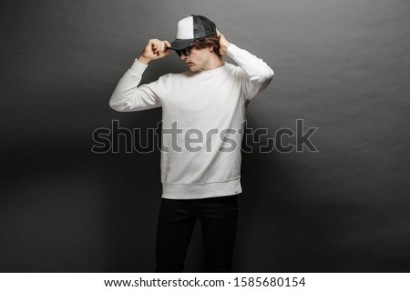 Man wearing blank white sweatshirt and empty baseball cap standing over gray background. Sweatshirt or hoodie for mock up, logo designs or design print with with free space. #1585680154