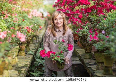 Beautiful woman watering plants and gardening in greenhouse. Florist working and taking care of the plants and flowers. Botanical garden, flower farming, horticultural industry concept #1585690678