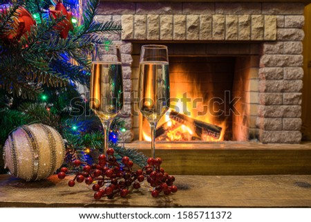 Christmas eve. Cozy fireplace. Champagne wine before Christmas tree decorated toys and christmas lights in country cottage.