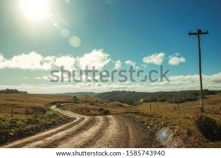Dirt road passing through rural lowlands called Pampas with hills and sunlight near Cambara do Sul. A small country town in southern Brazil with amazing natural tourist attractions. Retouched photo. #1585743940
