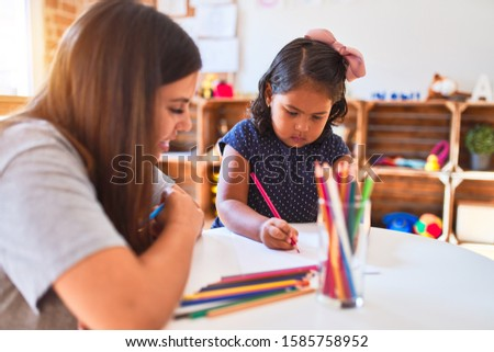 Beautiful teacher and toddler girl drawing draw using colored pencils at kindergarten #1585758952