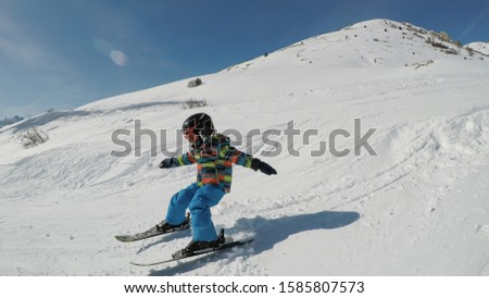 Little boy skiing. A 5 year old child enjoys a winter holiday in the Alpine resort.  #1585807573