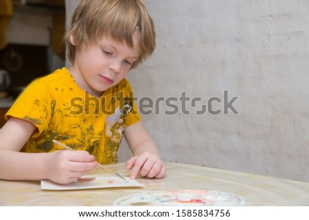 The child learns to draw. A boy of European appearance draws. Photos of real people. #1585834756