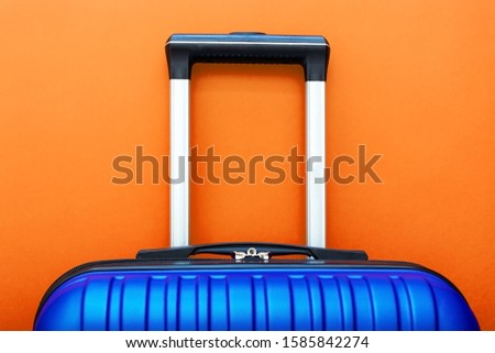 Modern Phantom Blue classic blue suitcase on Lush Lava background close up copy space for text. Minimal style travel concept. Vacation trip. Summer holiday stock photo. Trendy color 2020 classic blue