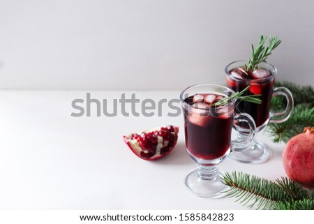 Two glass of pomegranate Christmas cocktail with champagne, soda and rosemary on a white table. Xmas drink. Close up. Copy space. Horizontal orientation. Horizontal orientation. #1585842823