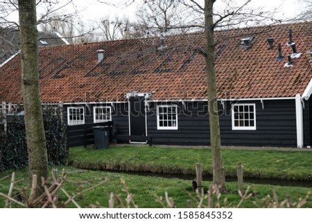 Beautiful vintage tiled roofs. Architecture old wooden houses Zaandam, Netherlands 03.18.2019 #1585845352