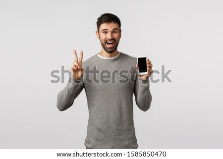 Friendly and carefree funny bearded gay man in grey sweater edit profile picture online dating app, make peace sign, showing smartphone display and smiling happily, standing white background