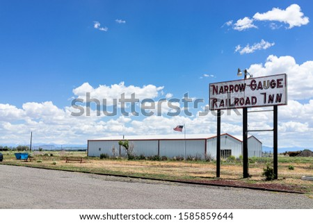 Antonito, USA - June 20, 2019: Highway 285 in Colorado with old vintage town building and sign for narrow guage railroad inn motel hotel #1585859644