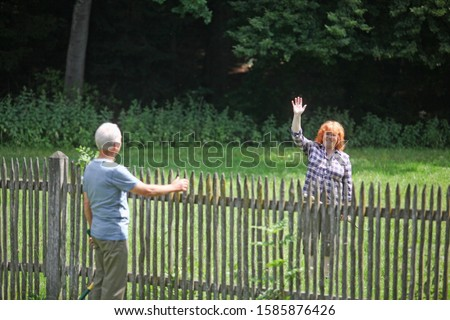 Neighbors greeting each other over fence Royalty-Free Stock Photo #1585876426