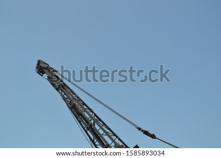 A low  angle view of a grey crane with wires under a blue sky #1585893034
